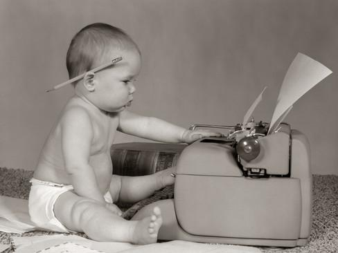 1960s-businesslike-baby-with-pencil-behind-ear-typing-on-typewriter